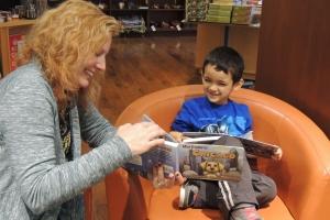 """Cuando Reji preside eventos y autografía libros, se asegura de que cada niño y niña obtenga un tiempo de lectura uno a uno con ella. Reji y este pequeño de Chicago disfrutaron juntos """"Max Explora Chicago"""" en Barbara's Bestsellers en diciembre, 2014."""